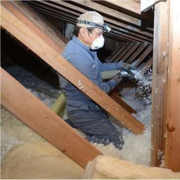 man applying blown-in attic insulation