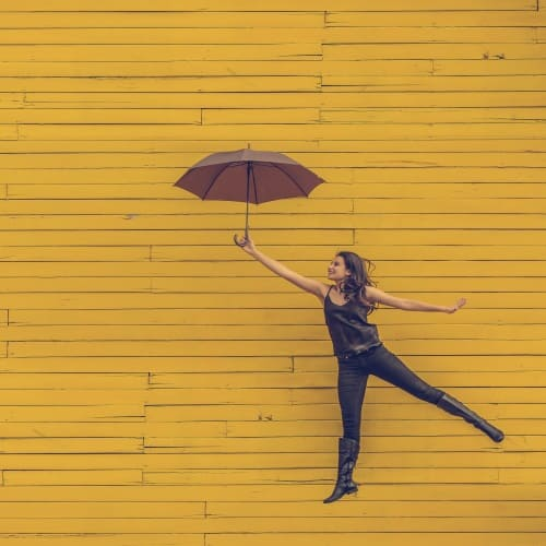 happy woman jumping with umbrella in front of cheery yellow wall