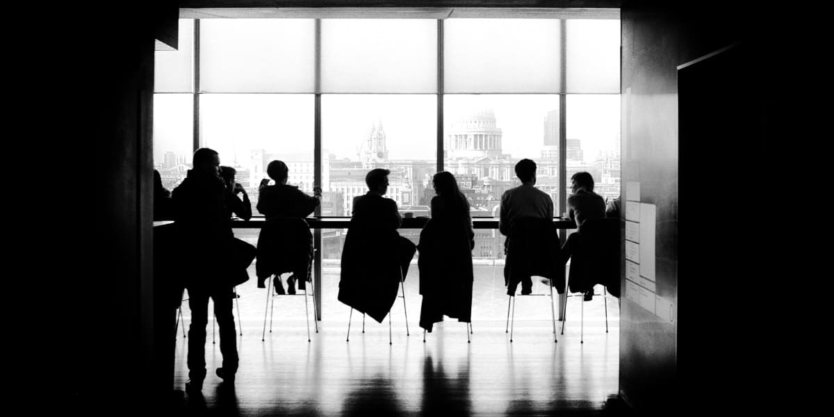 people sitting on chairs in meeting space with large window