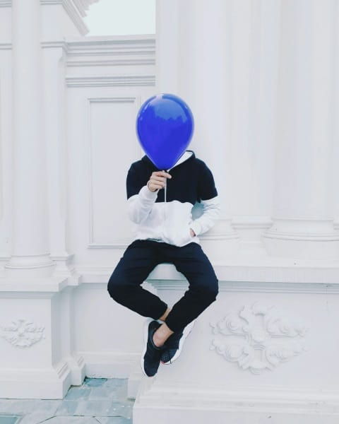 person holding a balloon obscuring their face