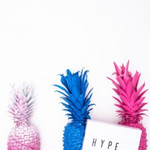 funky colored pineapples with hype placard