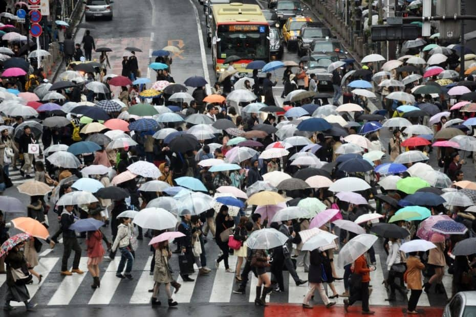 busy crosswalk of people with umbrellas (traffic)